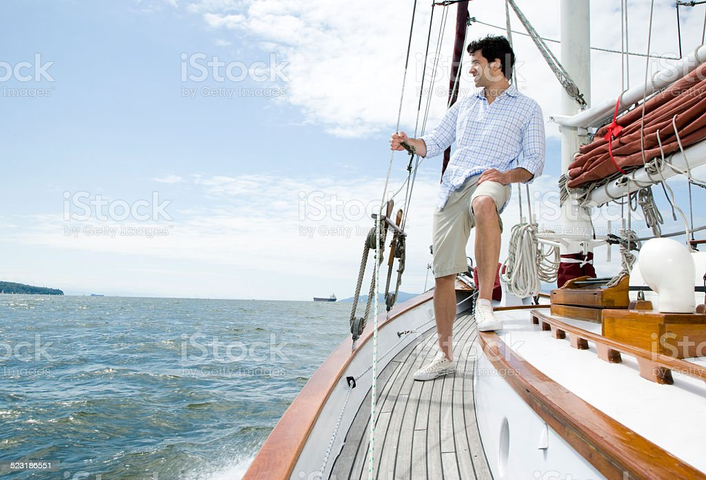 Man standing on deck of sailboat stock photo