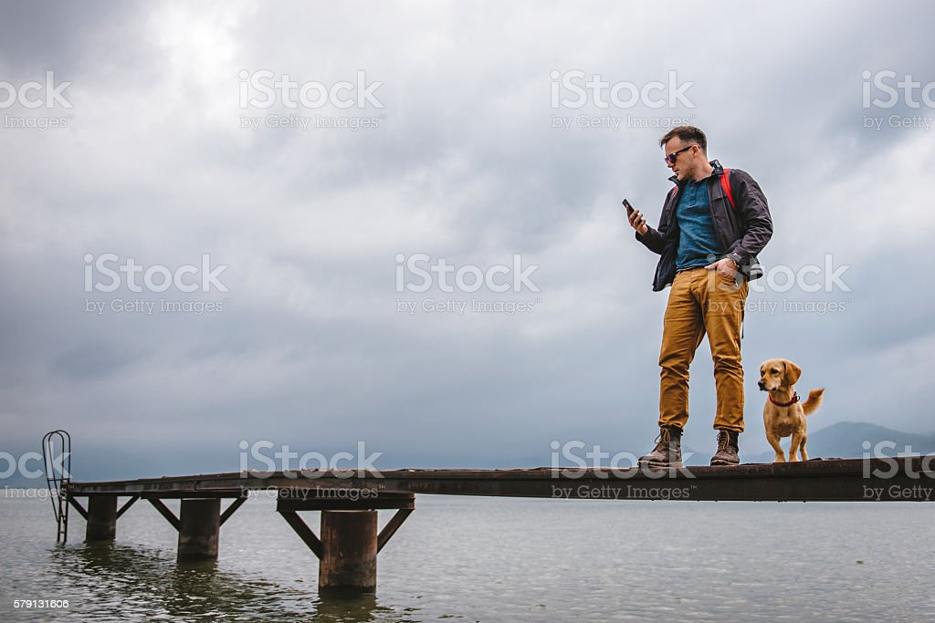 Man standing on dock and using smart phone stock photo