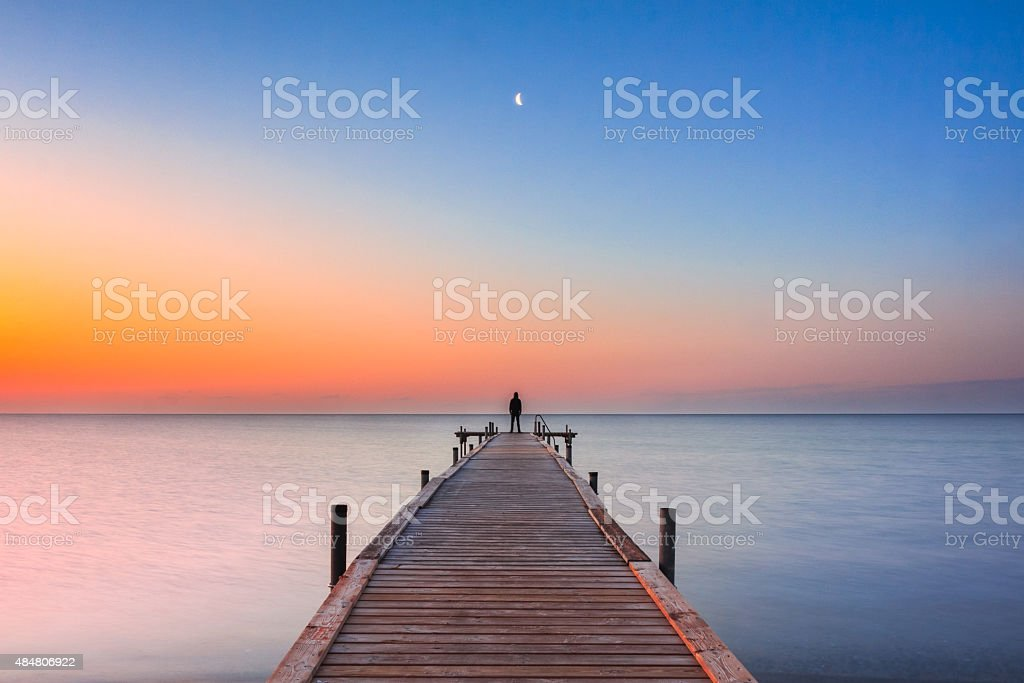 Man standing on jetty at beach with sunrise and moon stock photo