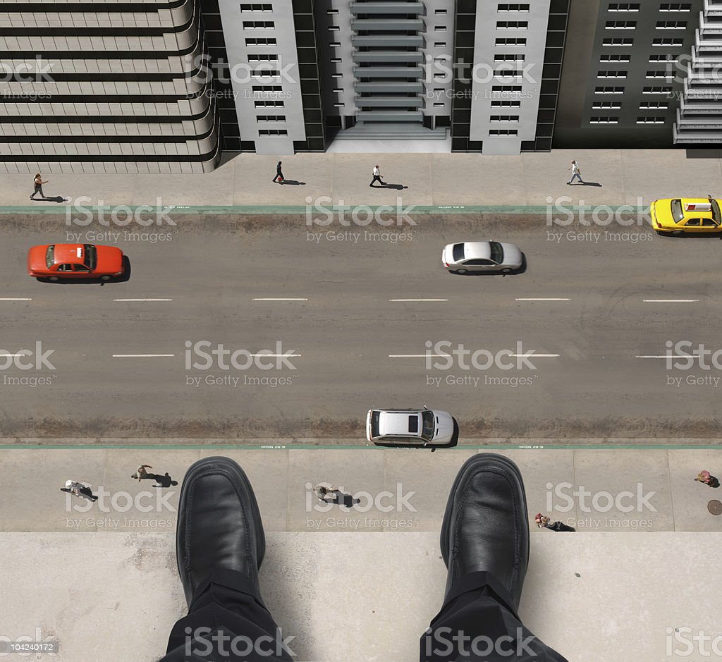 Man standing on ledge of tall building looking down stock photo