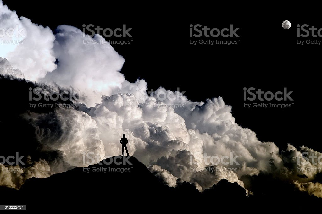 Man standing on mountain silhouetted against turbulent storm clouds stock photo