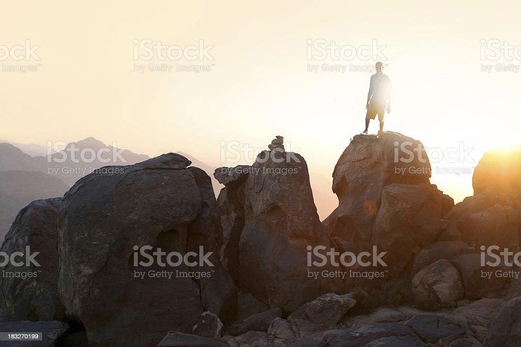 man standing on mountain summit stock photo
