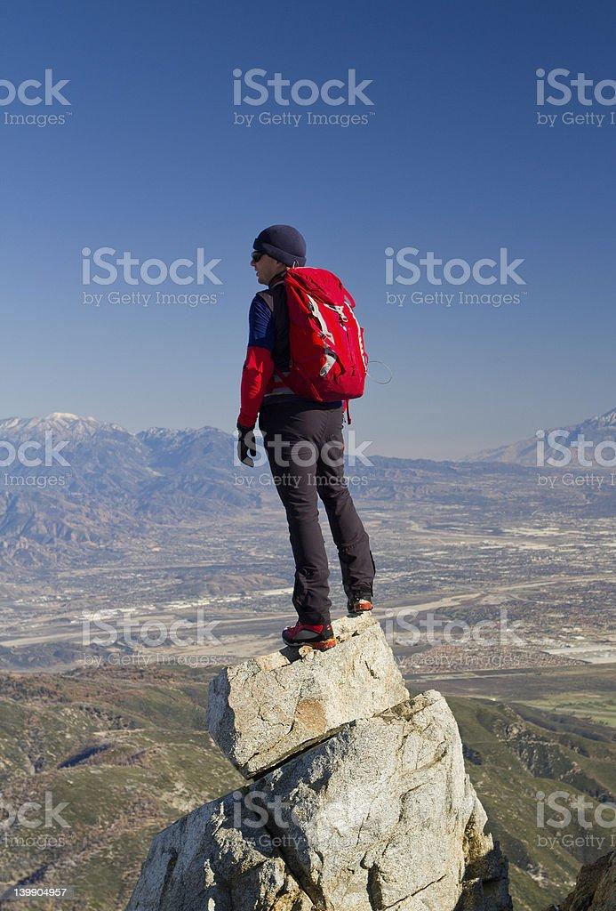 Man standing on mountain top overloking the horizon stock photo