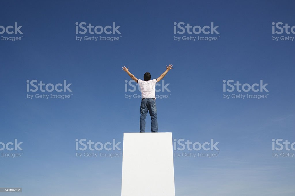 Man standing on pedestal or wall with arms up and blue sky royalty-free stock photo