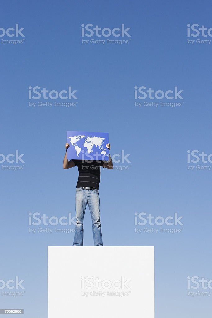 Man standing on pedestal outdoors with world map royalty-free stock photo