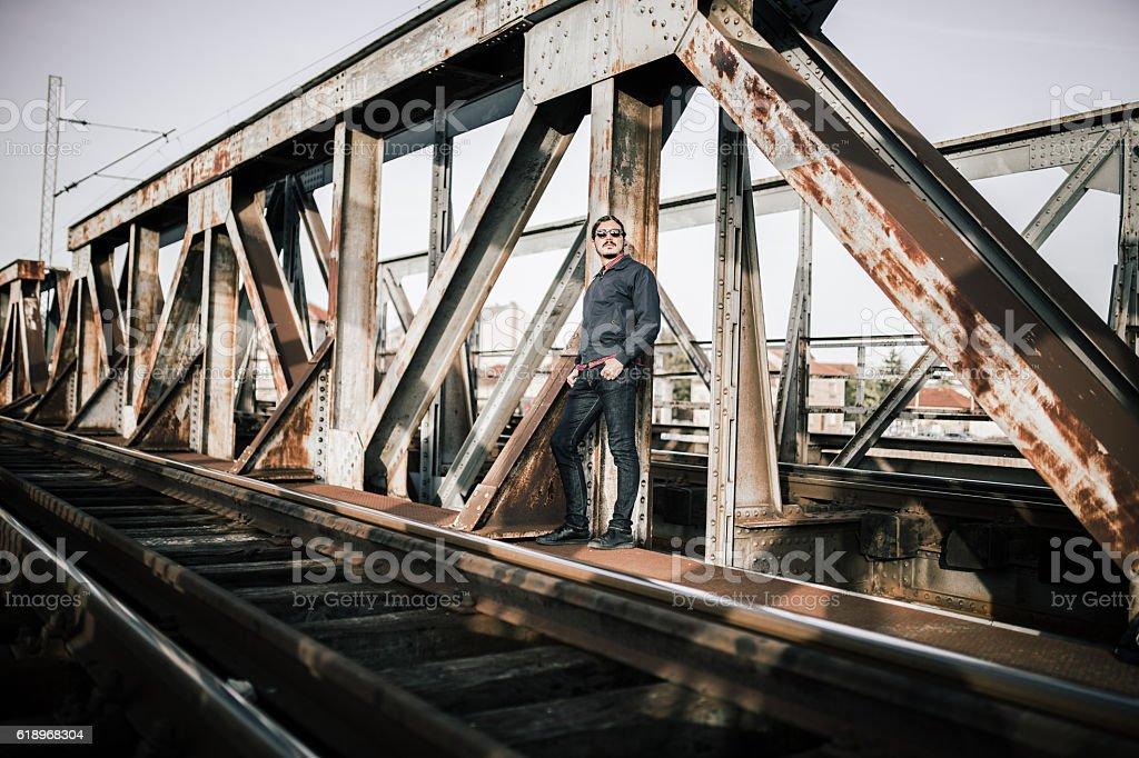 Man standing on railway bridge stock photo