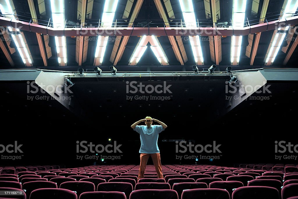 man standing on red velvet seat in empty auditorium royalty-free stock photo