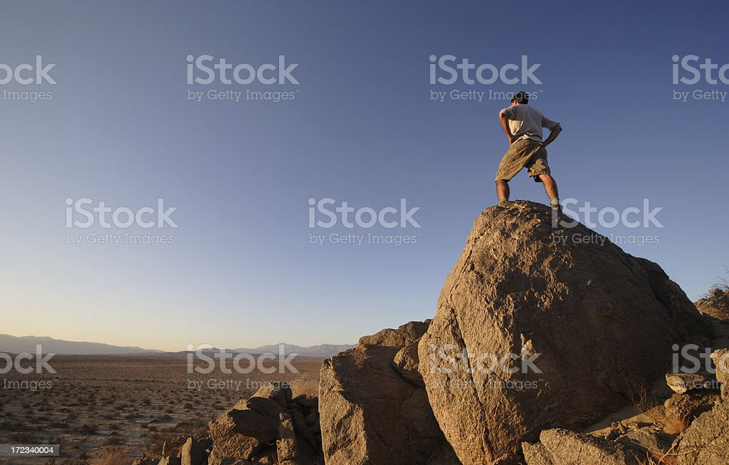 Man Standing on Rock Summit in Desert royalty-free stock photo