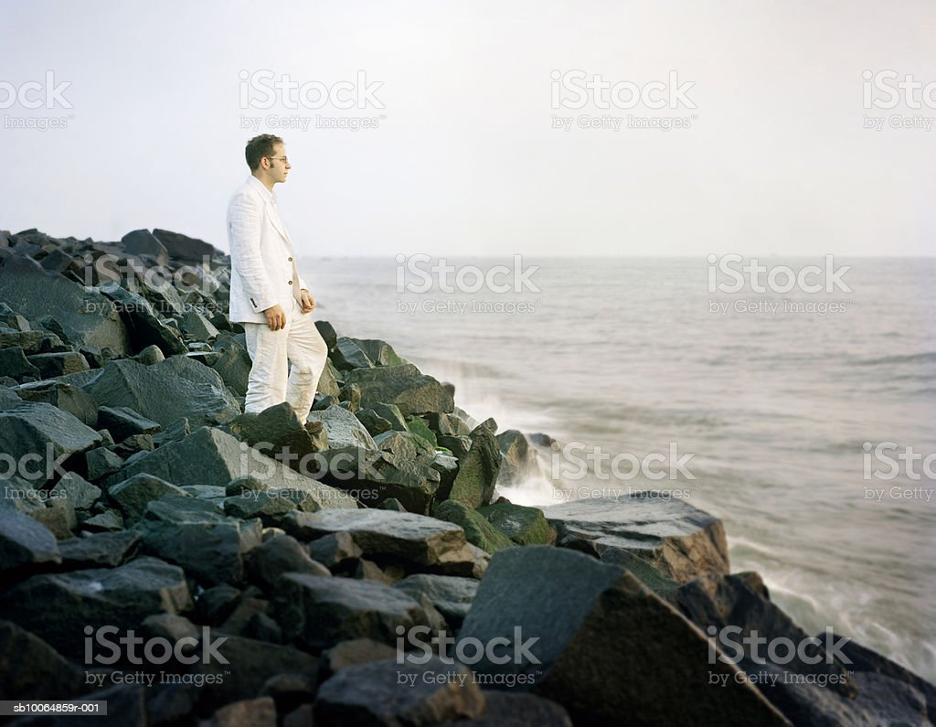 Man standing on rocks at sea, side view stock photo