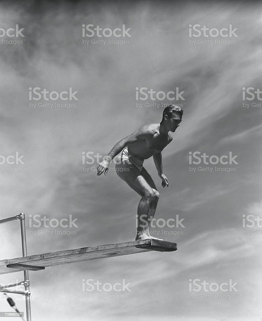 Man standing on springboard, preparing to dive, (B&W) stock photo