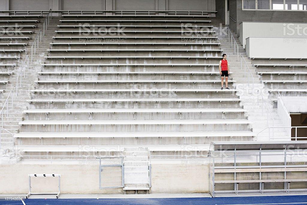 Man standing on stadium steps stock photo
