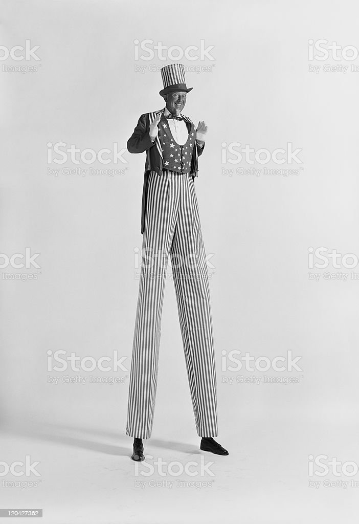 Man standing on stilts, smiling, portrait stock photo