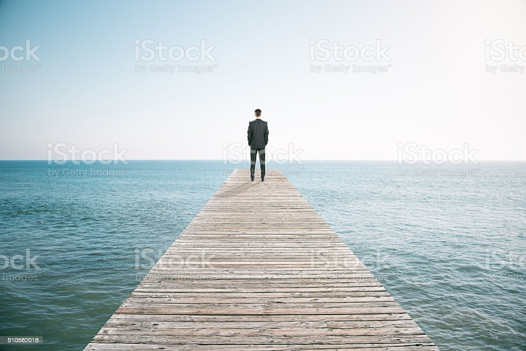 Man standing on the pier and looking into the distance stock photo