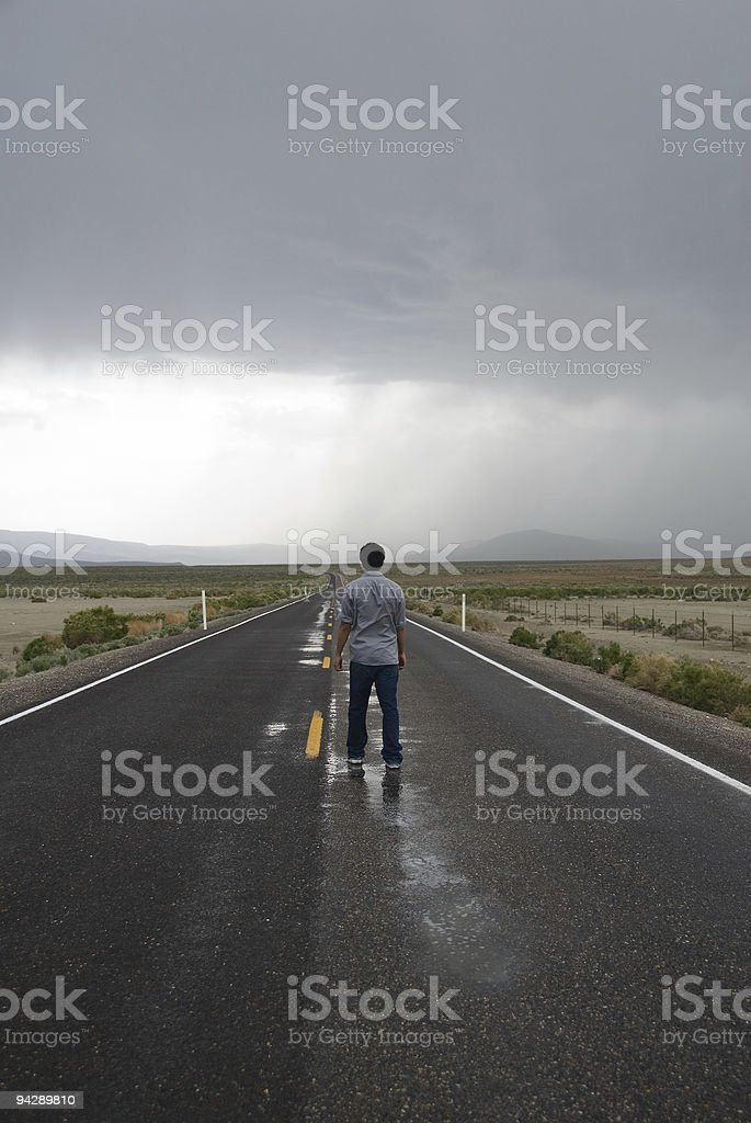 Man standing on the road looking at approaching storm royalty-free stock photo