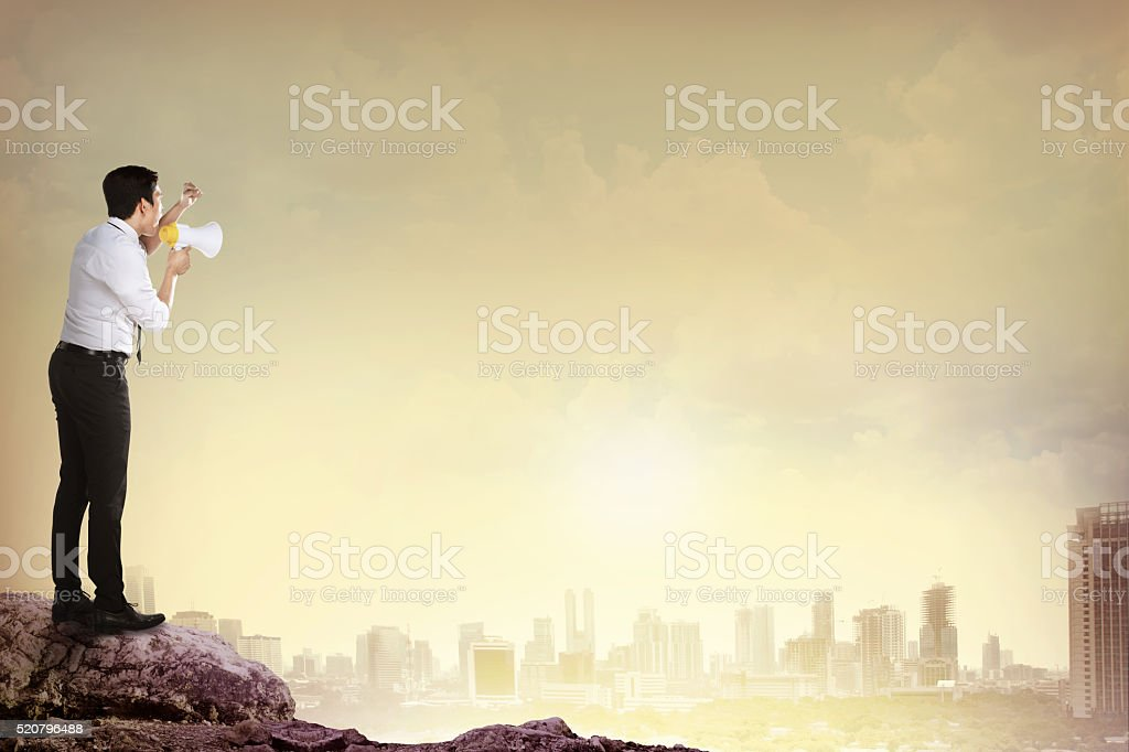 Man standing on the top of mountain, yelling using megaphone stock photo