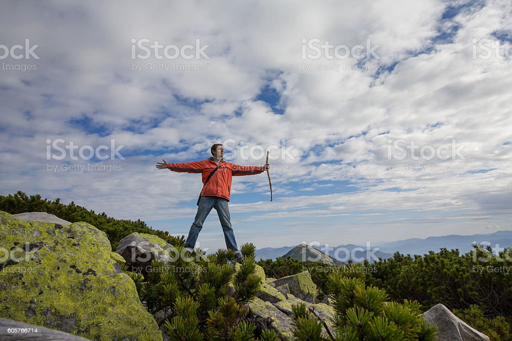 Man standing on the top of the mountain. Tourism stock photo