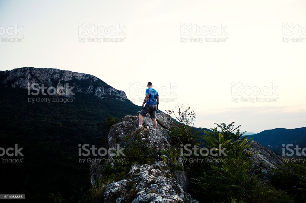 Man standing on top of a tall cliff. stock photo
