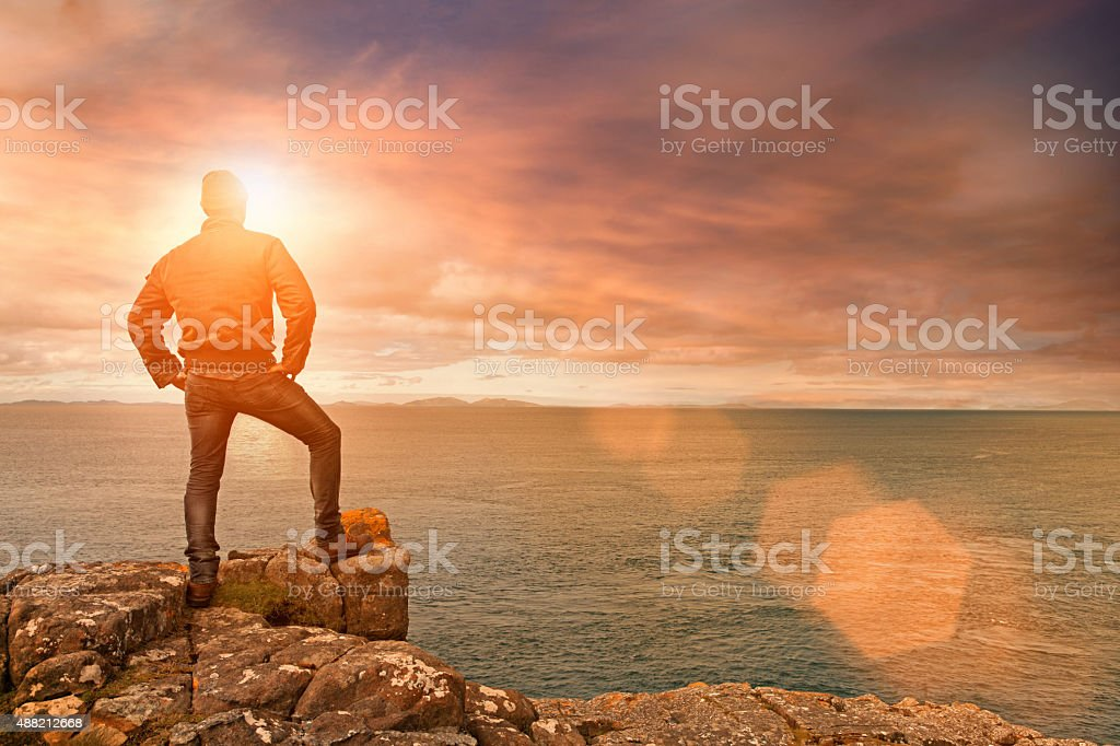 Man standing on top of sea cliff at sunrise stock photo