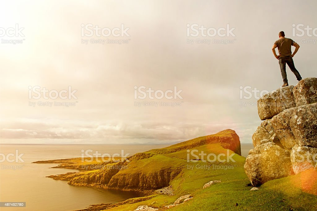 Man standing on top of sea cliff peak at sunrise stock photo