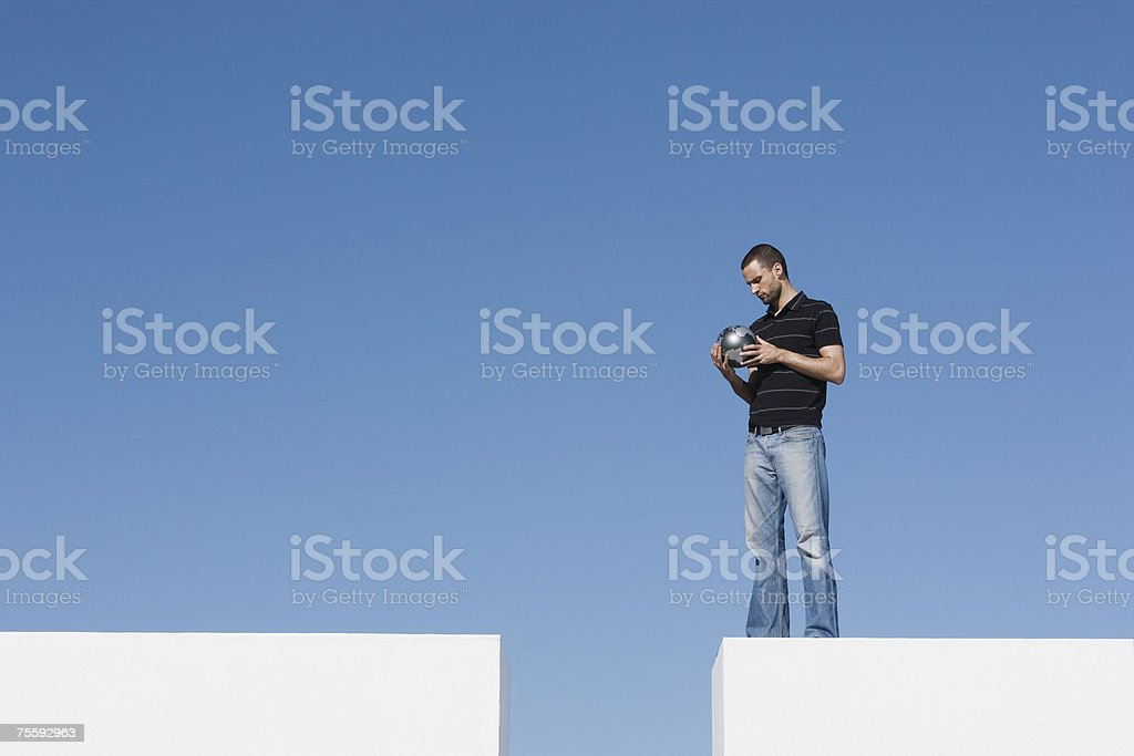 Man standing on wall outdoors holding globe royalty-free stock photo