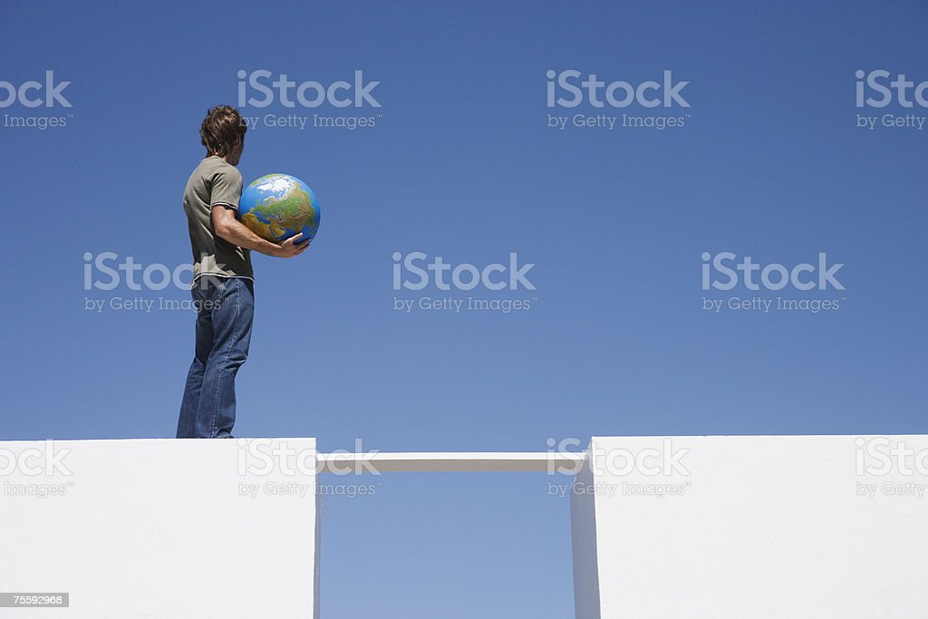 Man standing on wall outdoors with globe royalty-free stock photo