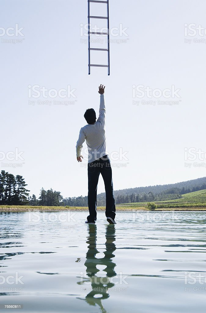 Man standing on water reaching for ladder rear view stock photo