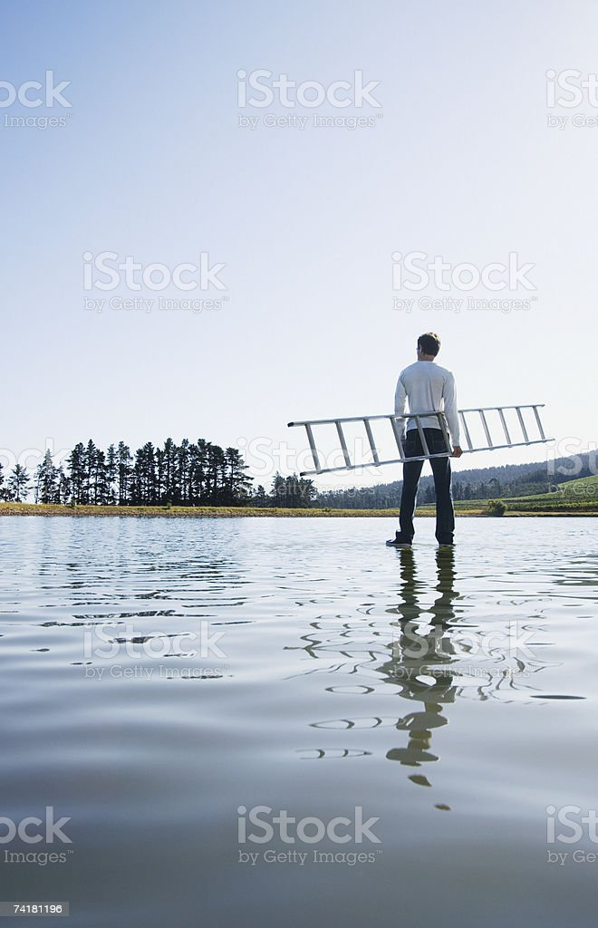Man standing on water with ladder royalty-free stock photo