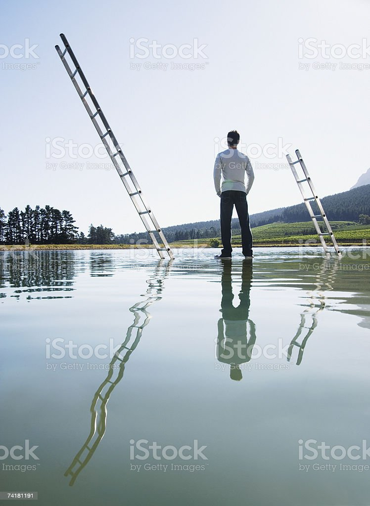 Man standing on water with ladders royalty-free stock photo
