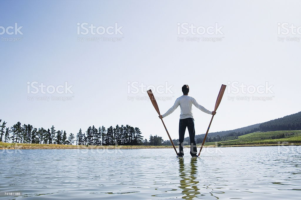 Man standing on water with oars royalty-free stock photo