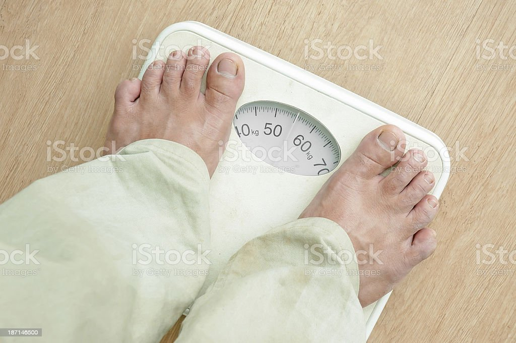 Man standing on weight scales with bare foot royalty-free stock photo