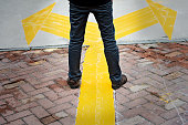 Man standing on yellow direction arrow