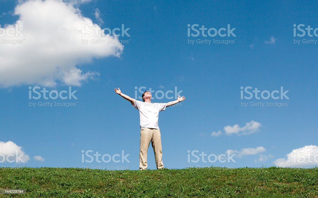 Man standing outdoors with arms spread under blue sky royalty-free stock photo