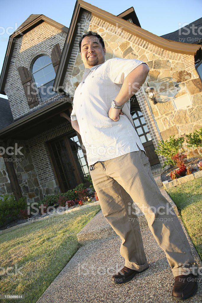 Man Standing Proudly In Front Of His New Home royalty-free stock photo