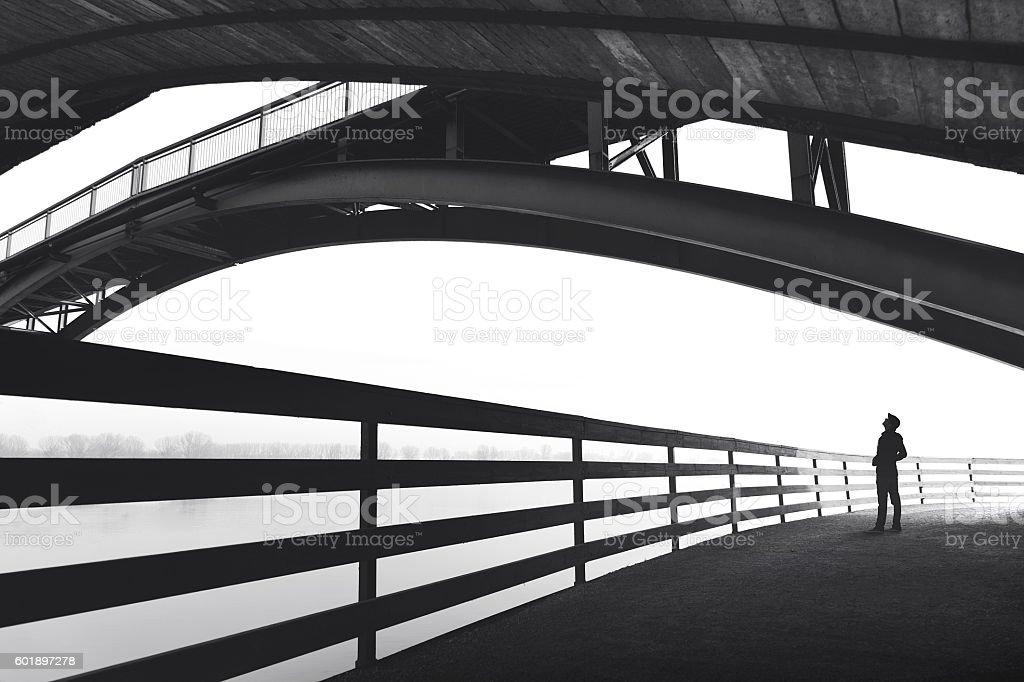 Man standing under bridge arch stock photo
