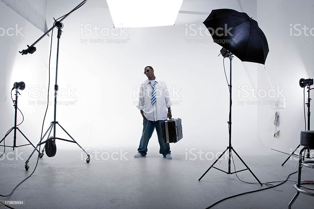 A man standing with a case in a white studio with lighting royalty-free stock photo