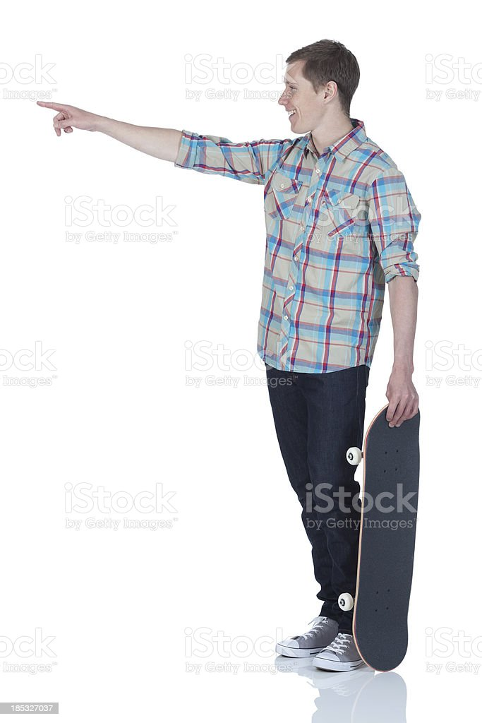 Man standing with a skateboard and pointing royalty-free stock photo