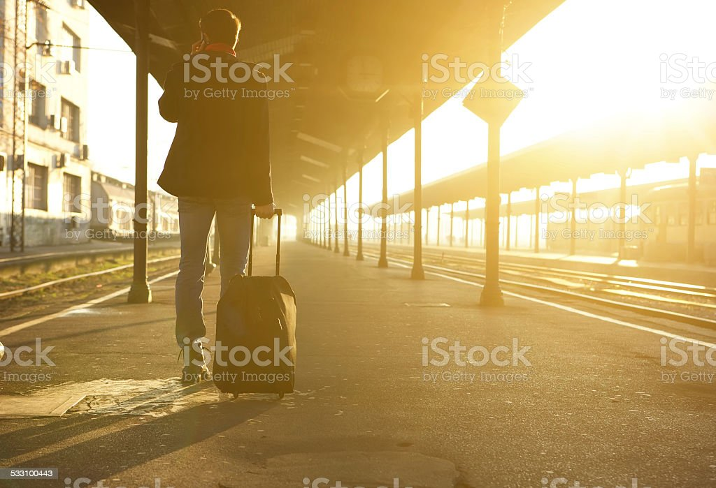 Man standing with bag and mobile phone at train station stock photo