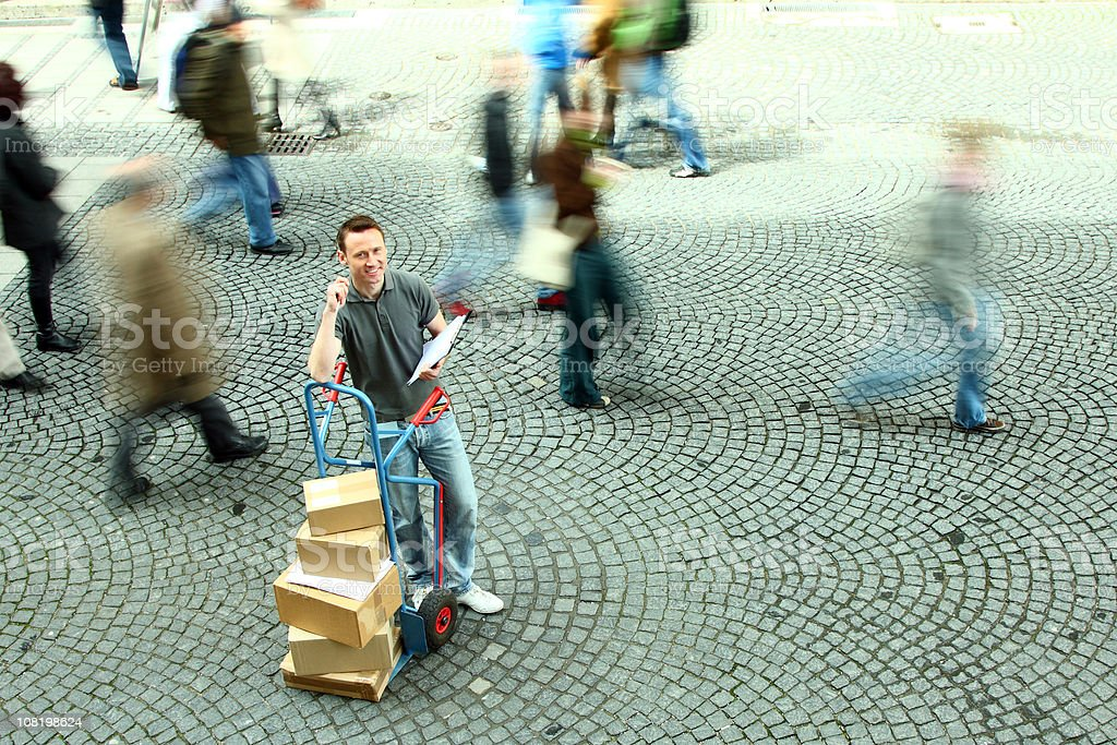 Man Standing with Dolly of Boxes While Crowd Walks By royalty-free stock photo