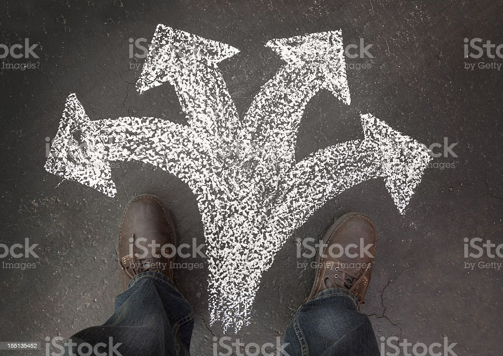 Man Standing with Four Paths to Choose stock photo