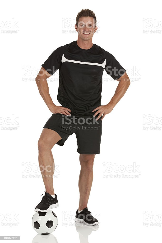 Man standing with his one foot on a soccer ball royalty-free stock photo