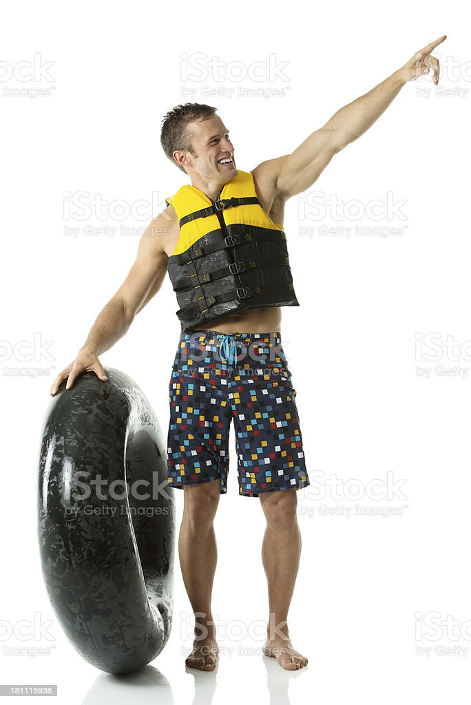 Man standing with inner tube pointing sideways royalty-free stock photo