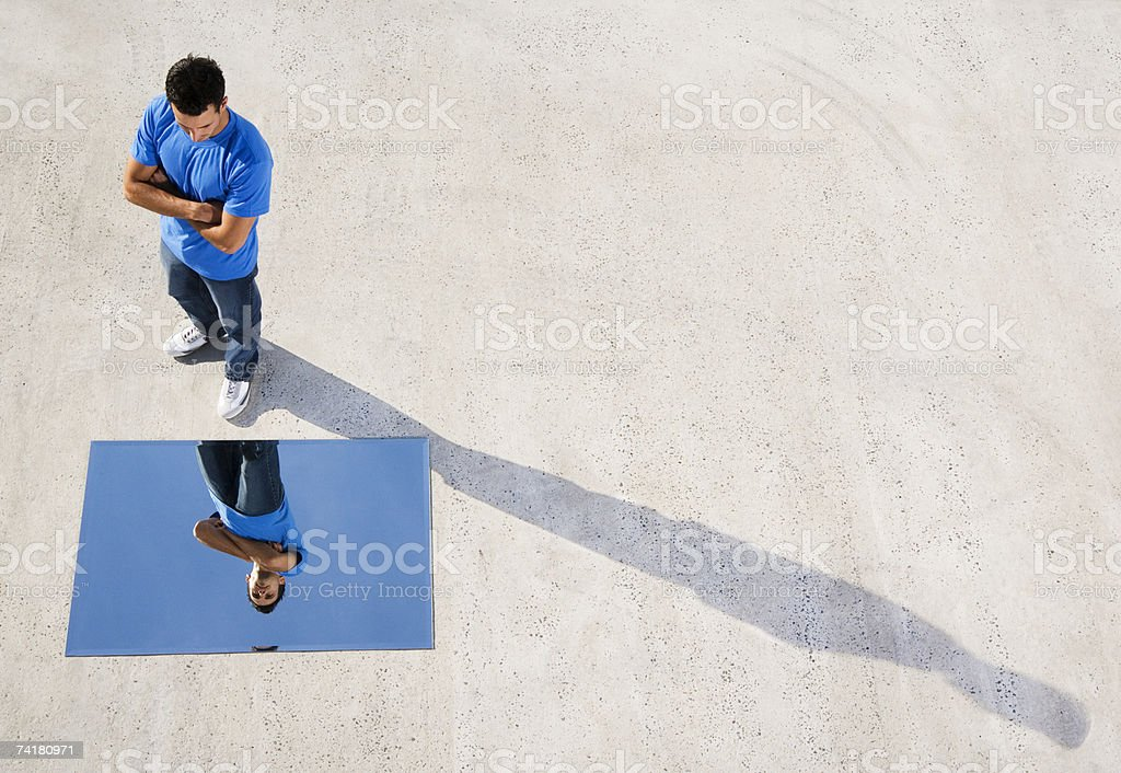 Man standing with mirror on ground and reflection stock photo