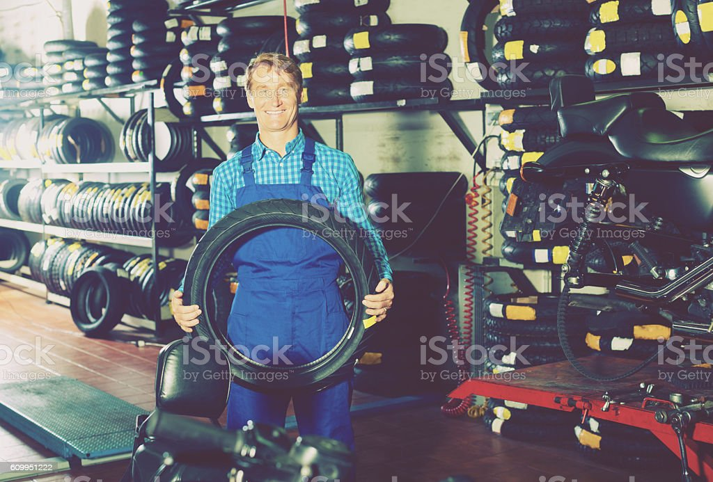 Man standing with new tires for motorbike stock photo