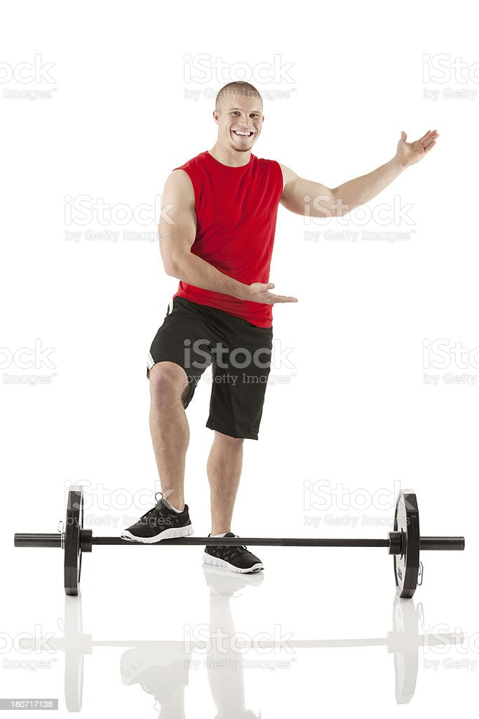 Man standing with one foot resting on a barbell royalty-free stock photo