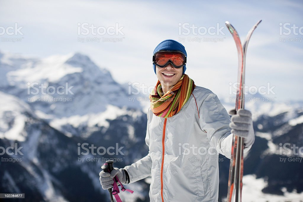 Man standing with skis on mountain top stock photo
