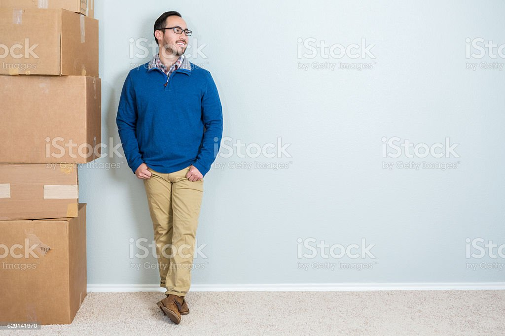 Man stands against blank wall with stack of boxes stock photo