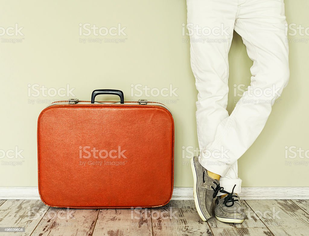 Man stands beside suitcase stock photo