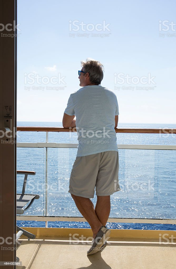 Man stands beside wooden railing, looks out to sea stock photo