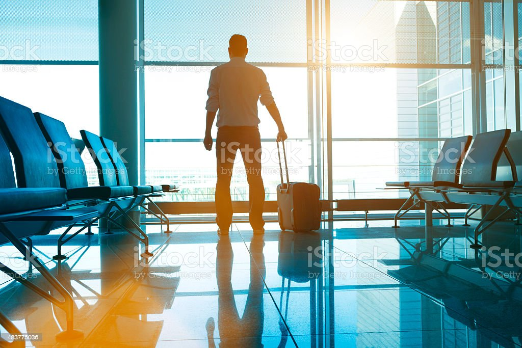 Man stands in airport with suitcase waiting for his plane stock photo