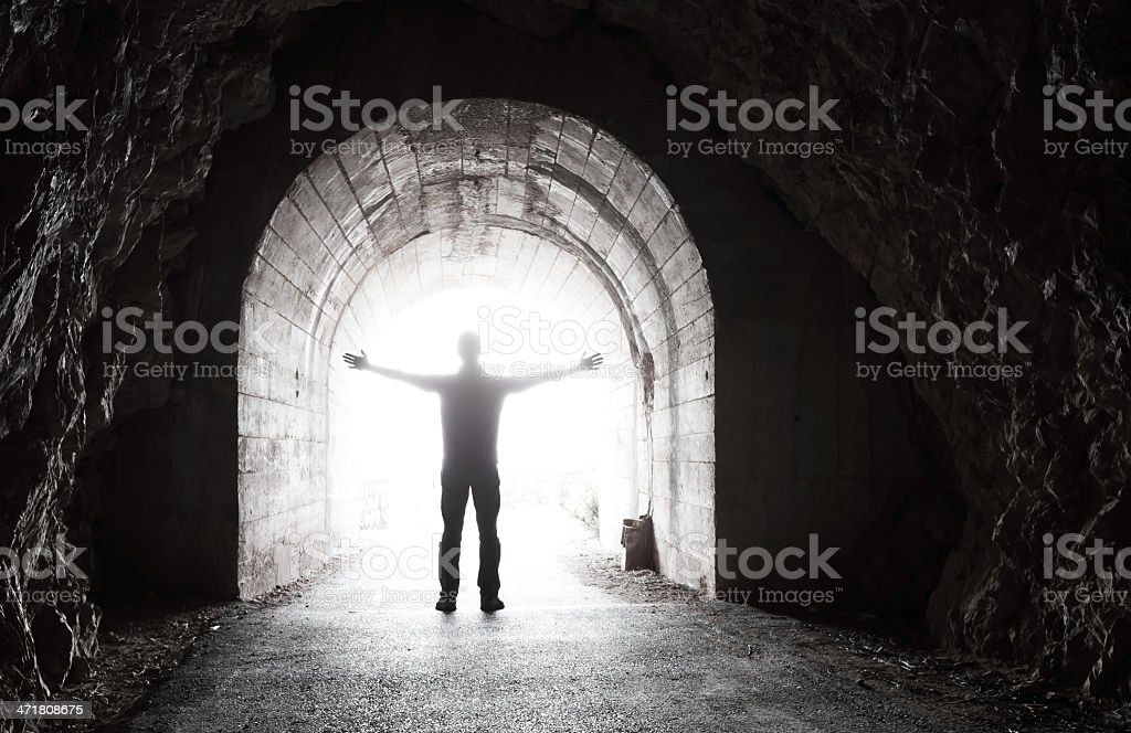 Man stands in dark tunnel with glowing end stock photo